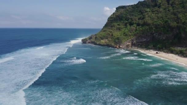 Aerial shot of ocean waves crashing coastline cliff, Bali, Indonesia