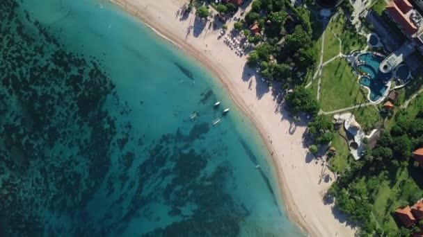 Luftaufnahme von blauem Wasser, weißem Strand und Hotels.