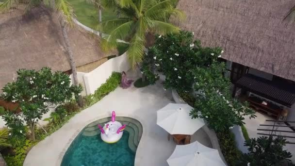 Woman in beautiful dress is passing in private tropical villa hotel near pool, aerial view.