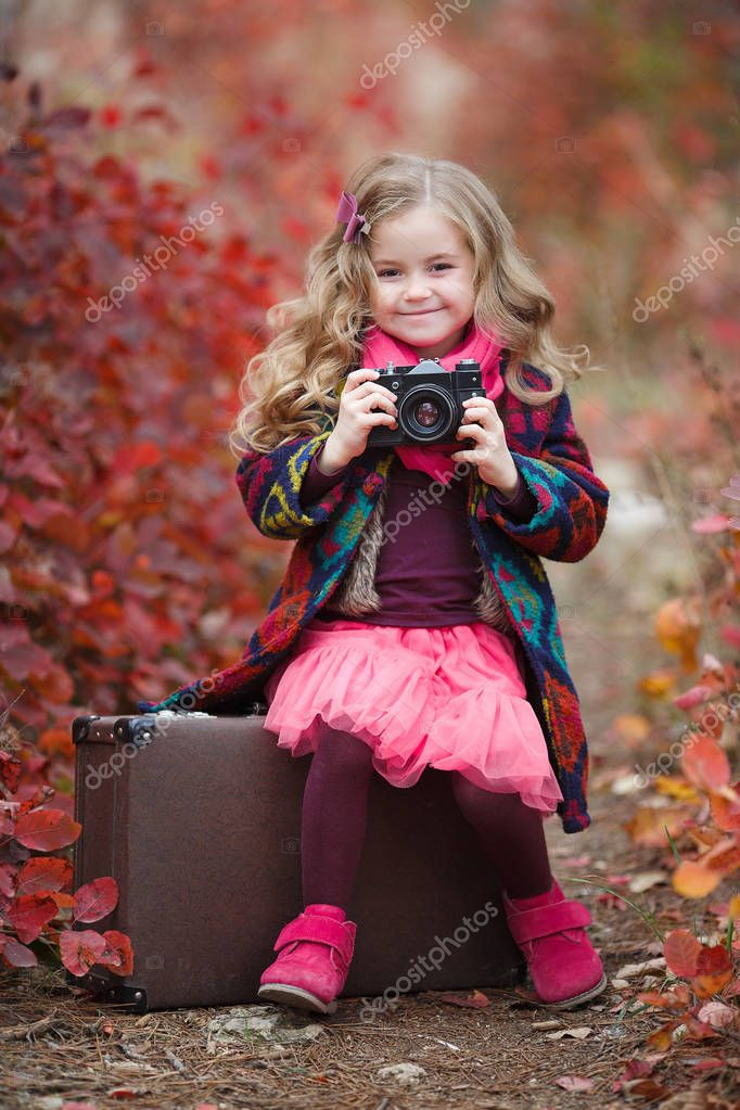 Little cute girl in an autumn jacket photographs the golden autumn, standing on the road in the woods with an old suitcase.Little kid is playing with camera and taking photo of autumn nature as master.Baby is in autumn park.