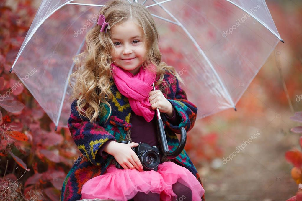Cute little girl playing with fallen golden leaves. Happy child walking in autumn park. Beautiful golden autumn time. Autumn kids fashion. Cute girl with an old suitcase and an umbrella in her hand on a footpath in the autumn forest during the rain.