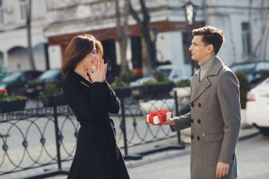 Holidays and events. A gift for the woman he loved.Couple in love. Family couple of man and sexy girl, trust. Slender man and woman with long blond hair, love. Relations of happy family, future. Loving couple in the city. Love and romance.