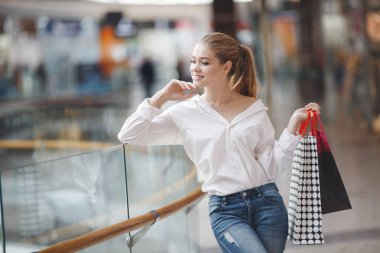 "Картина, постер, плакат, фотообои ""Black Friday and Boxing Day. Shopping gift and present on holiday. Beautiful women holding a shopping bag.Christmas Shopping and seasonal sale. Happy Girl in a white shirt holding multicolored paper shopping Bags. Shopping Center. Christmas Sales"", артикул 232153508"