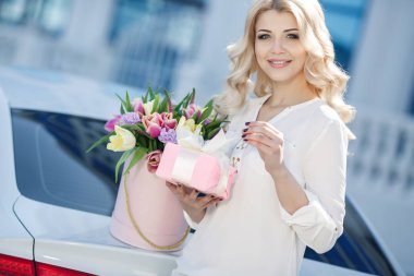 Girl with a large bouquet of multi-colored tulips . Happy woman on valentines day. Young beautiful woman with long curly hairs and blue eyes outdoors with a huge bouquet of beautiful flowers. Holidays and events. The concept of happiness.