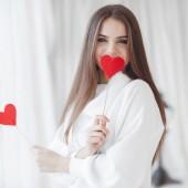 Fotografia Giorno di San Valentino. Bella giovane donna con cuore in sue mani. Giovane donna con cuore rosso su sfondo bianco. Ritratto di donna sorridente attraente su bianco studio girato con cuori. Ragazza allegra sveglia tiene a cuore di carta mani