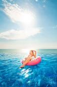 Letní dovolená. Žena v bikinách na matrace nafukovací prstenec v bazénu Spa.