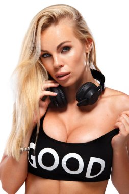 close-up portrait of beautiful sexy blonde DJ woman on white background in studio wearing headphones.