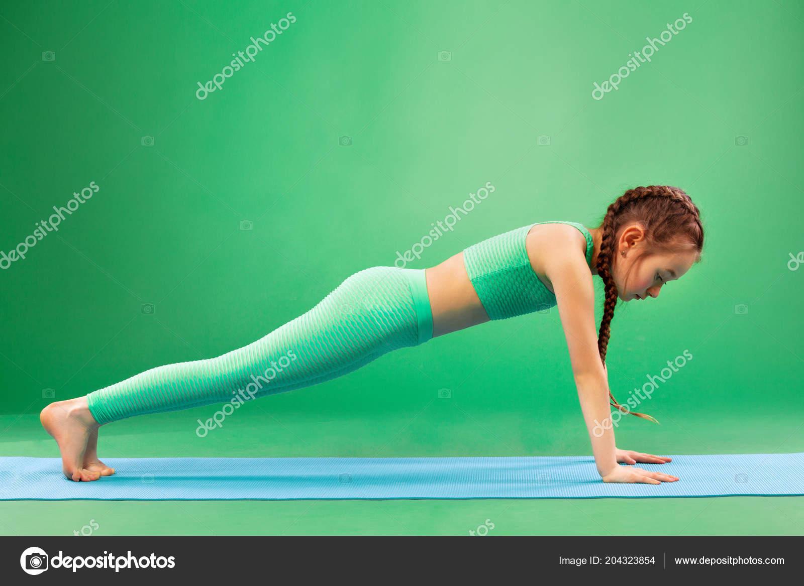 Kind Mädchen tun Fitnessübungen auf grünem Hintergrund — Stockfoto ...