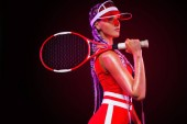 Tenista. Krásná žena sportovec s raketou v červený kostým a čepice izolované na černém pozadí. Móda a sport koncept.