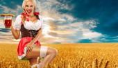 Bierparty. sexy Oktoberfestfrau - Kellnerin, in München in bayerischer Tracht, serviert große Bierkrüge auf goldenem Weizenfeld-Hintergrund.