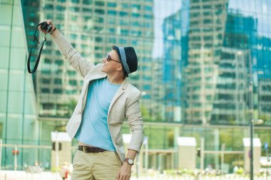 Man makes selfie in the big city against the background of skyscrapers. Travel and life style concept.
