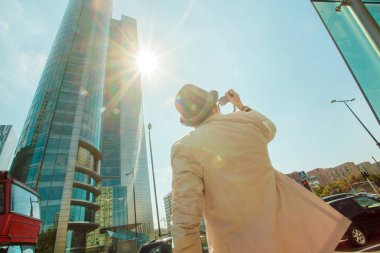 Man makes photo shoot of skyscrapers in the big city. Travel and lifestyle concept.