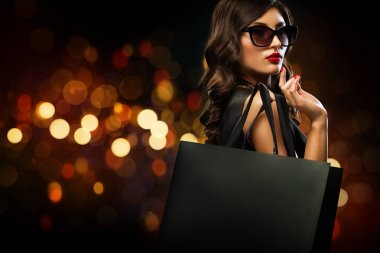 Beautiful young woman make shopping in black friday holiday. Girl with black bag on dark background. stock vector