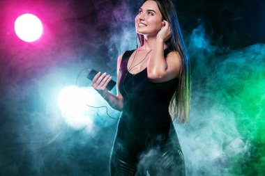 Beautiful young and woman in headphones listening music from phone and smiling. Color lights.