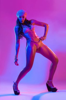 Fitness dancer and fashion model woman in bikini. Wet skin in colorful pink and blue neon lights, posing in studio. Beautiful girl, glowing make-up, colorful make up. Glitter vivid neon makeup.
