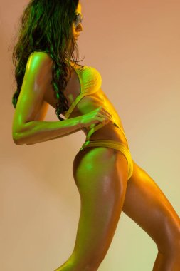 Fitness dancer and fashion model woman in bikini. Wet skin in colorful yellow and green lights, posing in studio. Beautiful girl, glowing make-up, colorful make up. Glitter vivid neon makeup.