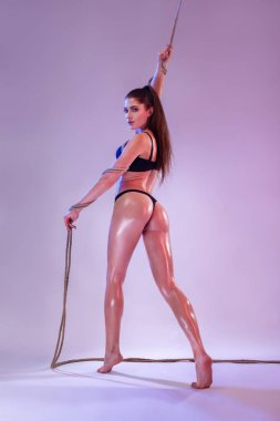 Beautiful young woman in lingerie dancing with a rope, studio shot