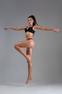 Fitness dancer and fashion model woman in bikini. Female with wet skin in lingerie posing in studio.