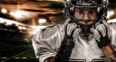 American football player. Sportsman with ball in helmet on stadium in action. Sport wallpaper. Team sports.
