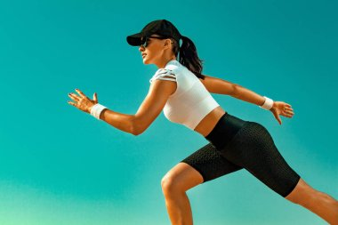 Sporty young woman and fit athlete runner running on the sky background. The concept of a healthy lifestyle and sport. Woman in black and white sportswear.