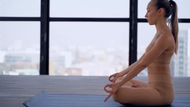 Yoga drinnen. Sportliche Erholung. schöne junge Frau in Hand mudra und namaste posieren für Meditation. Individuelle Sportarten. Nacktsportbekleidung.