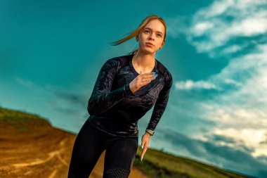 Fitness outside. Sporty young woman and fit athlete runner running on the sky background. The concept of a healthy lifestyle and sport. Woman in black sportswear.