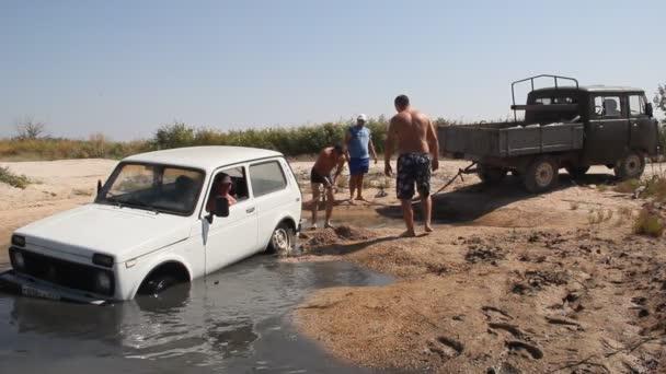 Primorsko-Achtarsk, Russia-25 agosto 2018: Persone e un camion ha tirato lauto fuori dallacqua. Lauto è bloccata in una grande pozzanghera