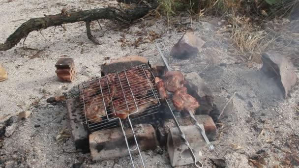 Vaření masa na uhlí. Grilování na písečném pobřeží