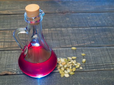 pumpkin oil in a glass decanter on a wooden table