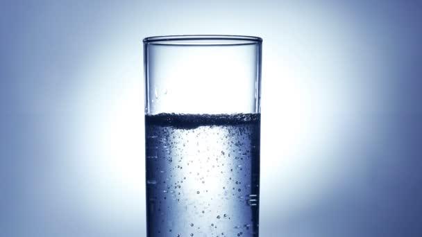 Malé vzduchové bublinky ve sklenici vody