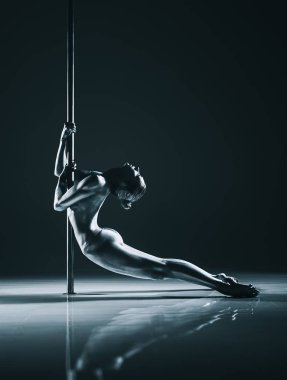 Young woman pole dancing. Silver body paint and toning. Dramatic colors.