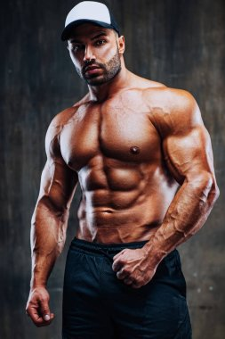Young strong man bodybuilder in cap on stone wall background