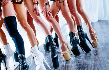 Big dancing girls team showing legs with high shoes