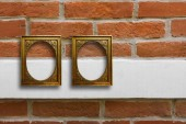 Fotografie Gilded wooden frames for pictures on old brick stone wall