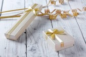 Fotografie Golden gift boxes with a bow on old vintage wooden table
