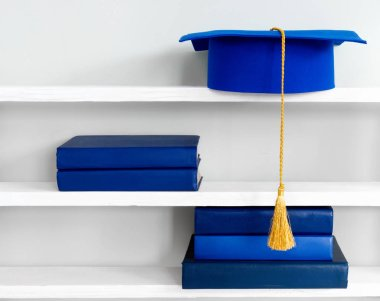 Graduation blue mortarboard on top of stack of books on wooden shelf on background of vintage wall