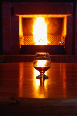 One glass of cognac on background of old brick fireplace
