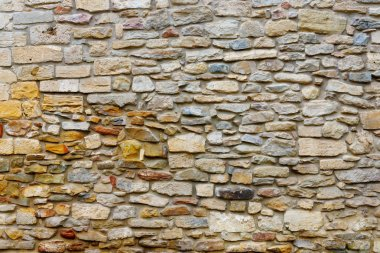 Texture collapsing stone wall of old house with brick masonry.