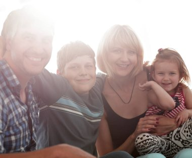 family with two children sitting together and looking at camera