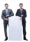 Fotografie two businessmen holding a blank banner