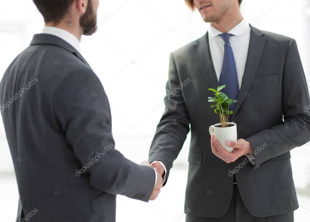 businessman with a sapling shaking hands with a partner.