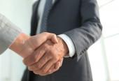 Fotografie Excited smiling businessman handshaking partner at meeting,