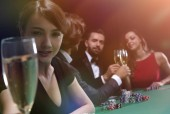portrait of smiling woman with drink playing poker