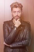 Fotografia moda uomo in giacca di pelle, fondo di legno