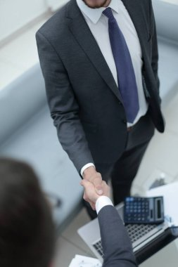close up.handshake trading partners over the desktop