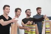 Gruppe junger Männer mit Einkaufstaschen