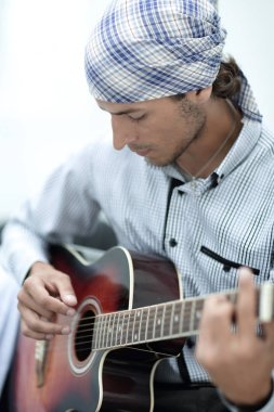 Young man in bandana playing the guitar
