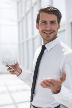 close up.smiling businessman with smartphone