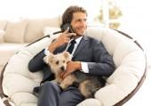 Erfolgreicher Geschäftsmann hält Hund und Haustier und spricht auf dem Smartphone