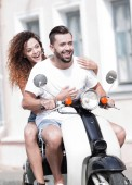 Photo Cool man and beautiful girl riding on  scooter with  expression
